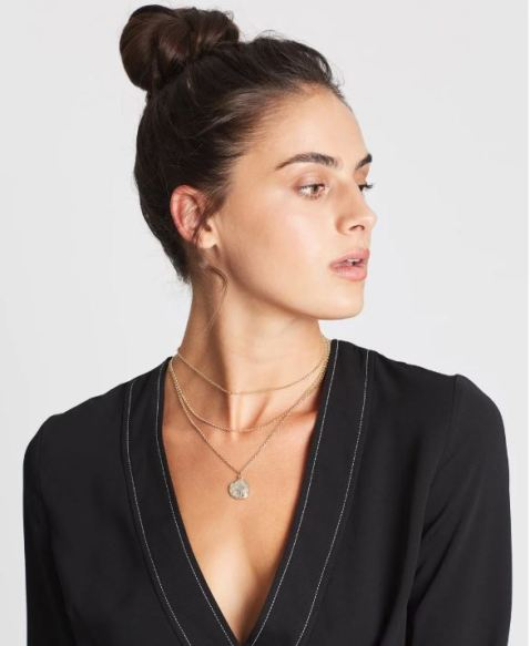 Female with dark hair, black shirt and a gold necklace