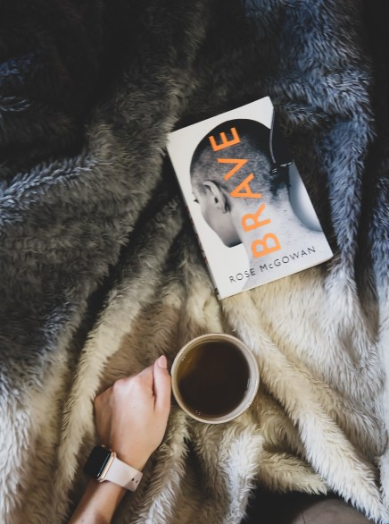 The book Brave by Rose McGowan sitting on a fluffy blue and cream blanket while a hand holds a cup of tea. Only the hand can be seen of the person.