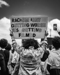 Photo by 99 Films of demonstrator during police violence protests 2020 holding sign