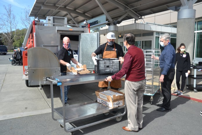 (Courtesy of Sally Hogarty)(L-R) Fourth Bore Tap Room and Grill General Manager Paul Jones, Fourth Bore's Bo Galindo, John Muir's Buddy Santoso and Chris Alessio unload meals from the 1971 Ford fire engine for frontline workers at John Muir's Concord campus.