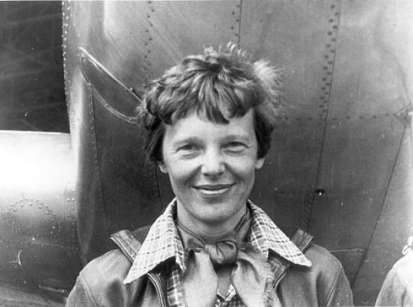 Amelia Earhart standing under nose of her Lockheed Model 10 E Electra