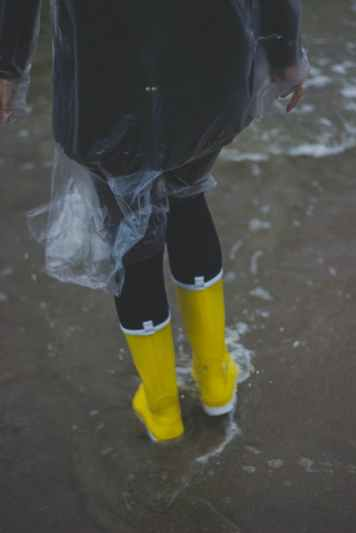 person wearing clear plastic raincoat and pair of yellow rainboots