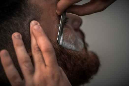 person holding gray straight razor