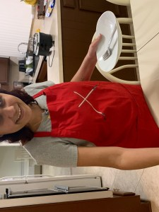 Nicole standing at the dinner table in her apron. She has a plate with utensils in her left hand and her right hand is placing a plate on the table. She is grinning