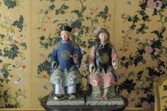 2 clay Chinese dolls, in front of very well-preserved 18th century silk wall covering.