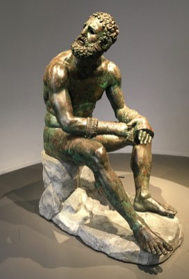 The Boxer At Rest is a stunning bronze sculpture, discovered in 1885 after being buried deliberately in antiquity in the dying days of the Roman Empire. The statue is a masterpiece of Hellenistic athletic professionalism, with a top-heavy over-muscled torso and scarred and bruised face, cauliflower ears, broken nose, and a mouth suggesting broken teeth.