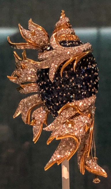 Designed as a circular-cut sapphire conch shell with diamond and yellow diamond swirl tip, extending pavé-set diamond and yellow gold foliage, circa 1957. A piece like this was sold at Christie's in 2018 for USD 68,750