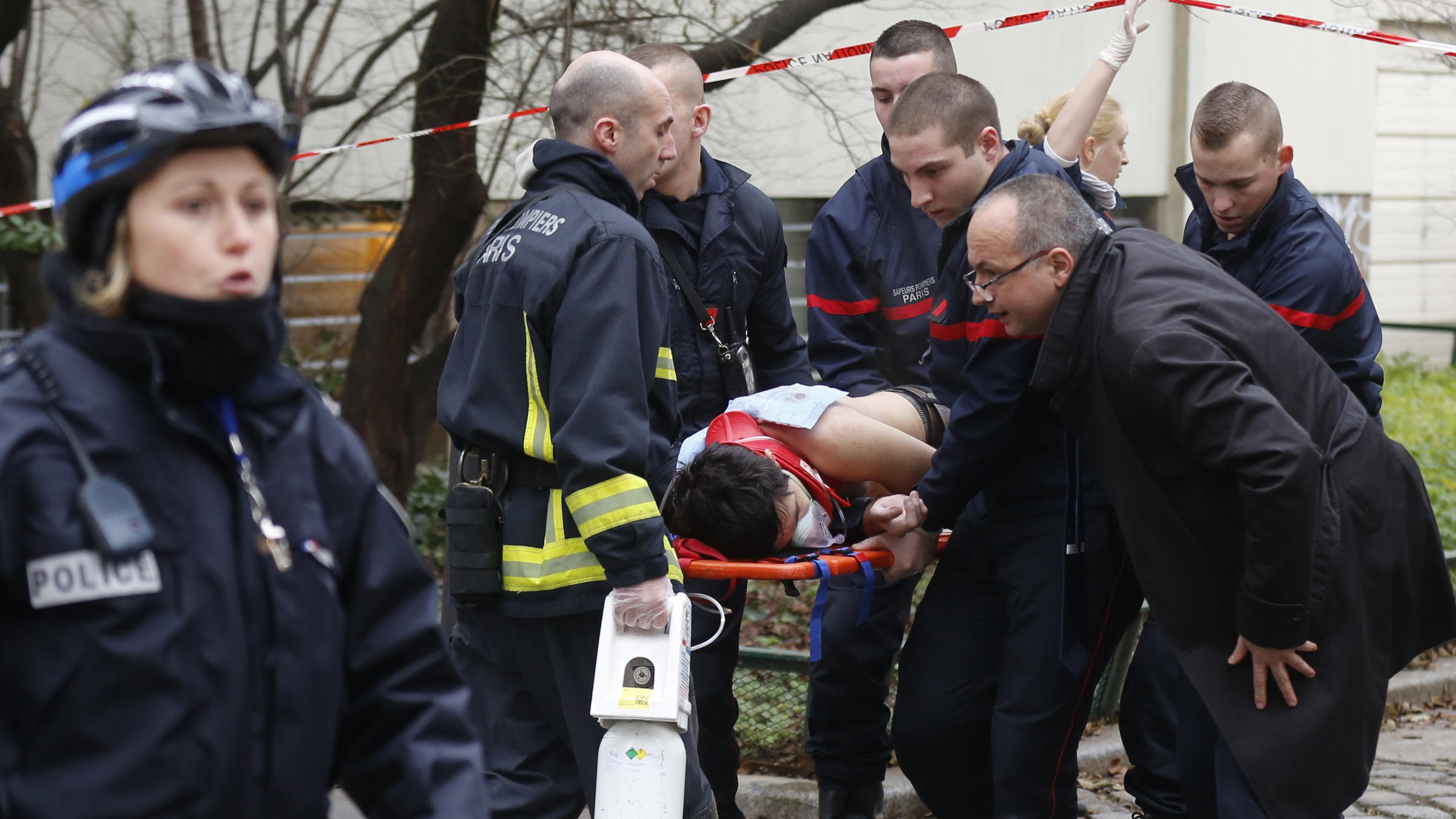 Firefighters carry a victim on a stretcher at the scene after a shooting at the Paris offices of Charlie Hebdo, a satirical newspaper,