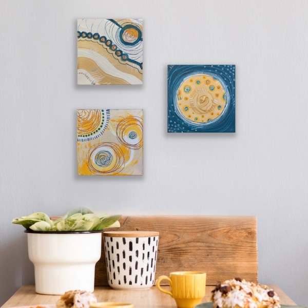 set of 3 abstract paintings above table