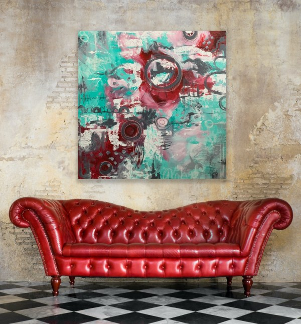 colorful abstract painting above red leather sofa