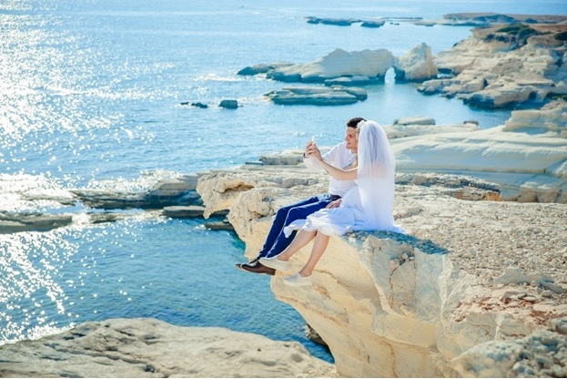 Newly married couple on a cliff