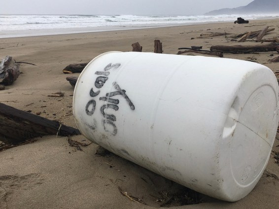White plastic barrel with locals only written on it; beach and surf in the background