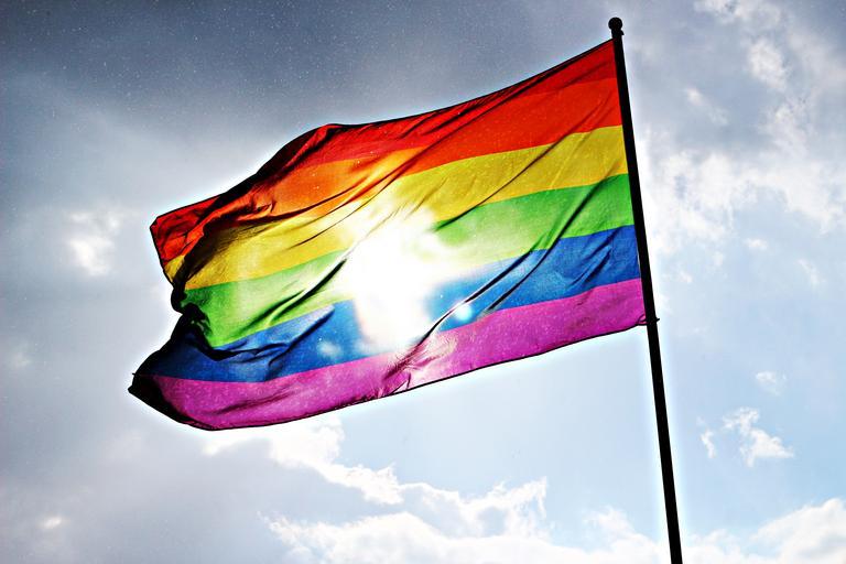 Sunlight shines through a rainbow flag.