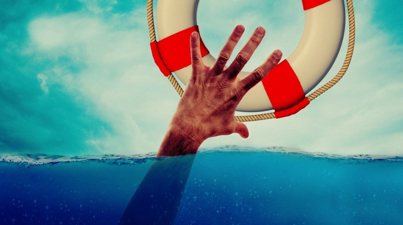 A hand reaches from under the water to grab a life preserver.