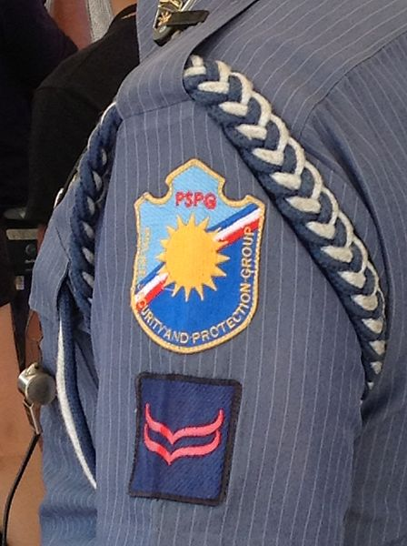 The shoulder of a Philippine National Police uniform. There is a braid around the shoulder, a badge for the Security and Protection Force, and a blue square badge with two red chevrons.