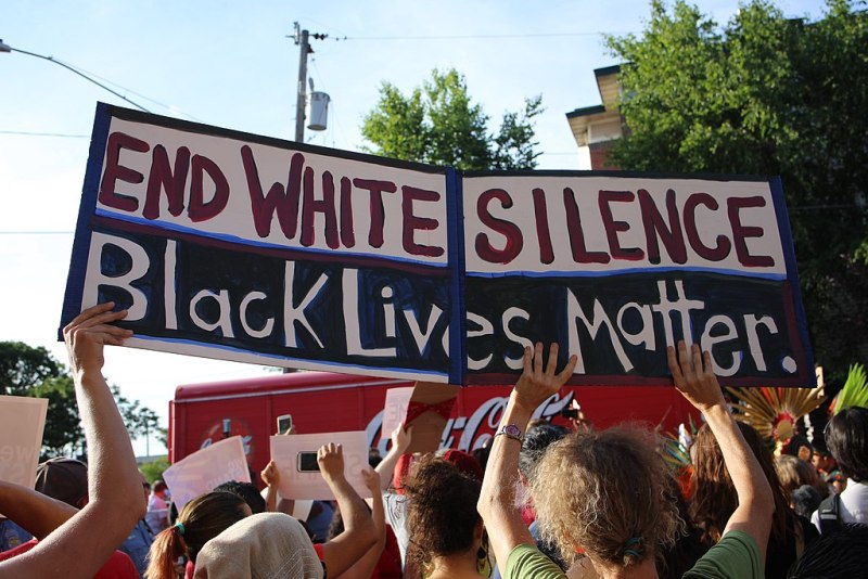 """A crowd of protestors. A large, two-toned sign reads """"End White Silence"""" and """"Black Lives Matter."""""""