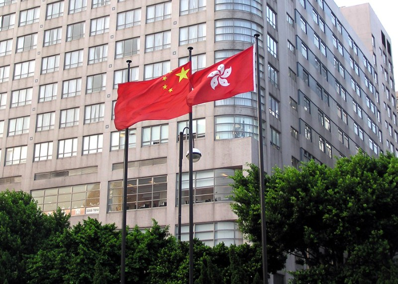 A larger Chinese flag flies behind a smaller Hong Kongese flag.