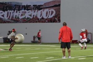 An OSU assistant prepares to throw a large balance ball at Demario McCall after he fields a punt.