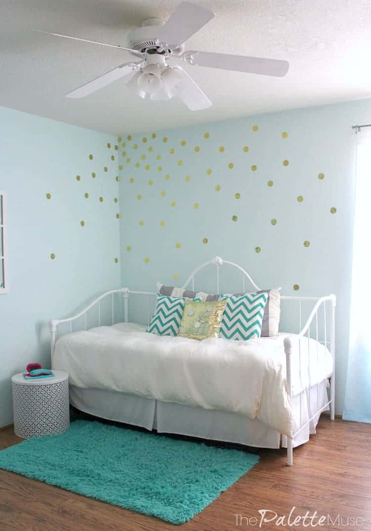 Fresh bedding and a gold vinyl polka dot wall treatment make this bedroom pop!