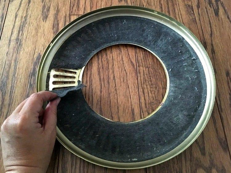 Peeling lint filter from ceiling fan cover.