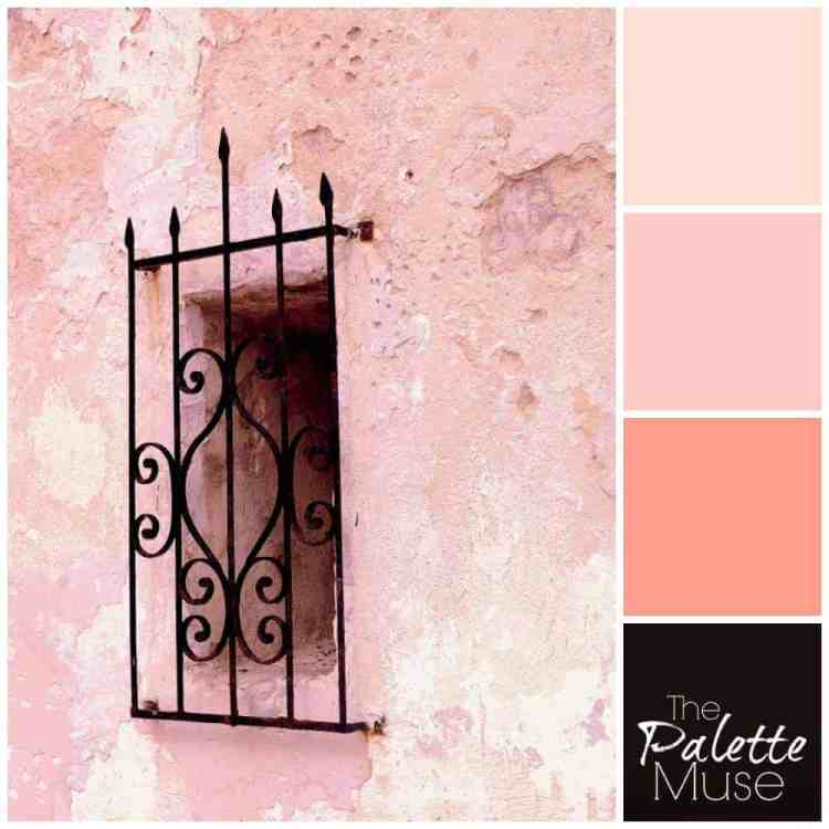 A dark window covered with black wrought iron peeks out of a layered pink plaster wall. #thepalettemuse #pinkpalette #colorinspo