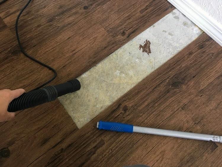 Repairing vinyl plank flooring - vacuuming under the plank you are replacing.