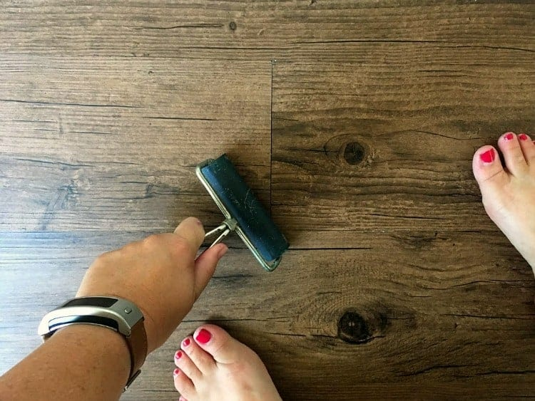 Using a roller to adhere vinyl plank flooring to the subfloor.