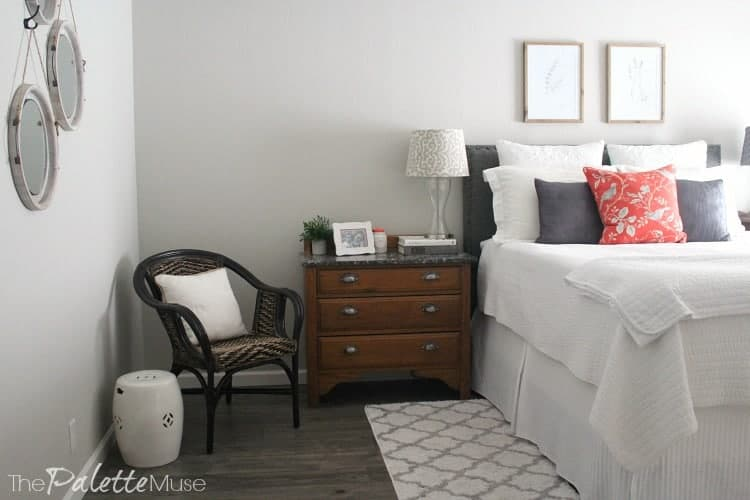 White bedding and wood dresser and chair in the corner of this master bedroom.