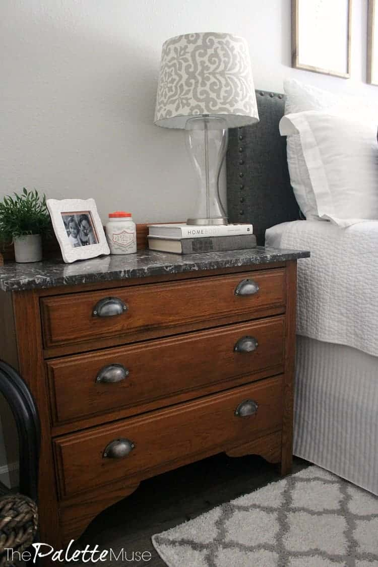 A craigslist-found dresser with the original marble top and updated drawer pulls serves as a nightstand. #bedroommakeover #nightstand #bedroomdesign