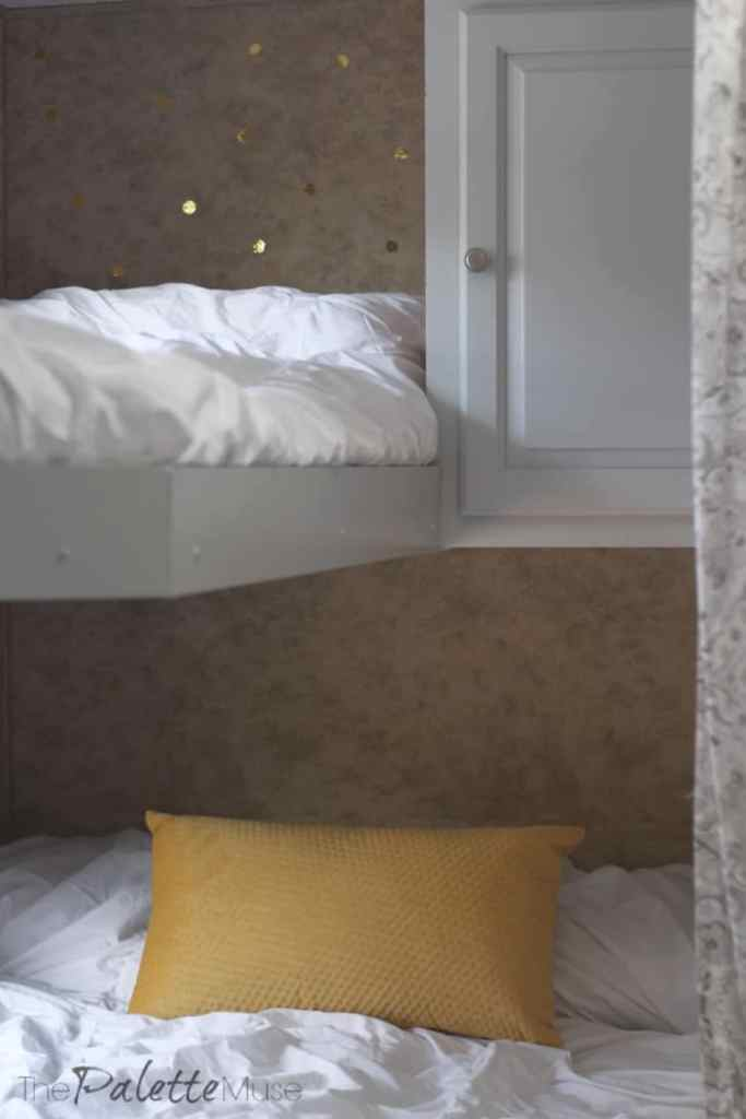 A glimpse of camper bunkbeds with white bedding and gold accents