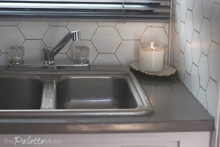 Gray countertop and sink with white and gold hexagon backsplash