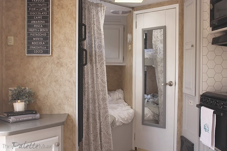 Camper interior with gray cabinets and white bedding