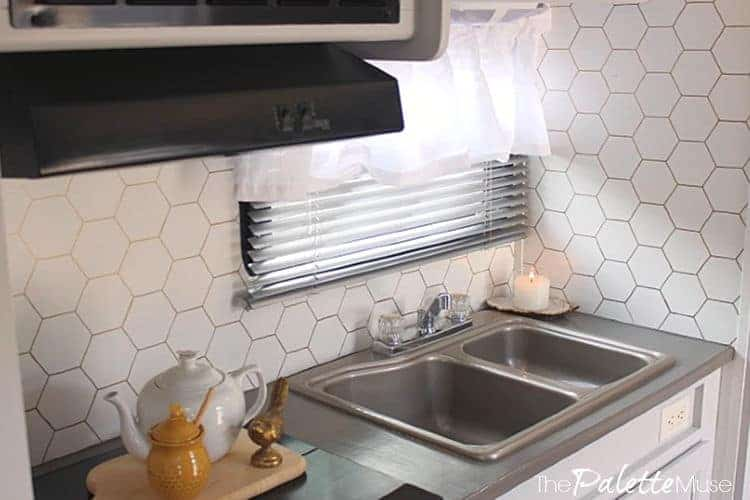 A DIY gold hex stencil backsplash casts a subtle glow over this tiny camper kitchen. #campermakeover #tinykitchen #minimalistkitchen