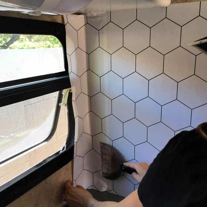 Applying removable wallpaper in gray on white hexagon pattern