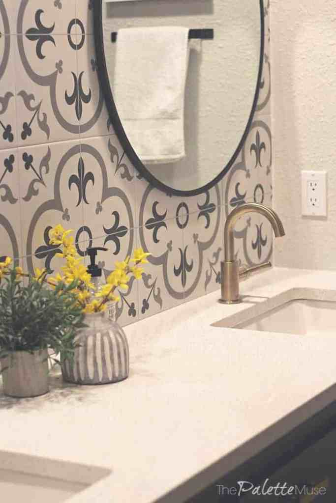 A modern bathroom countertop with brass fixtures, round black mirror, and patterned tile backsplash