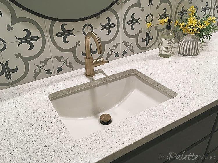 Brass sink faucet in front of patterned tile backsplash