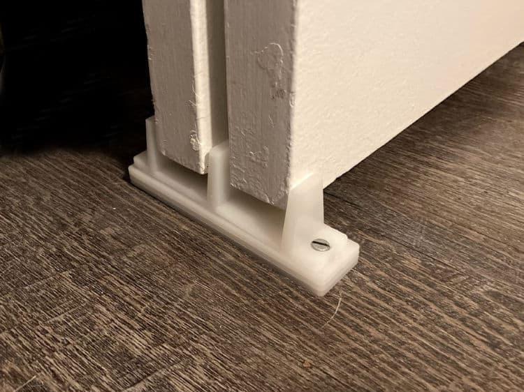 White plastic floor guide for two sliding closet doors.