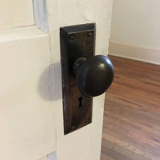 White door with historic dark bronze door handle and plate complete with keyhole