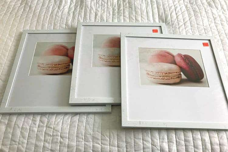 Three framed prints of pink macarons.