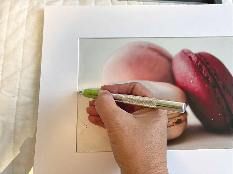 cutting a print out of a photo mat