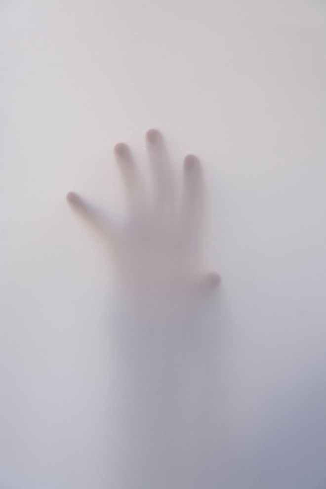 person s hand touching wall