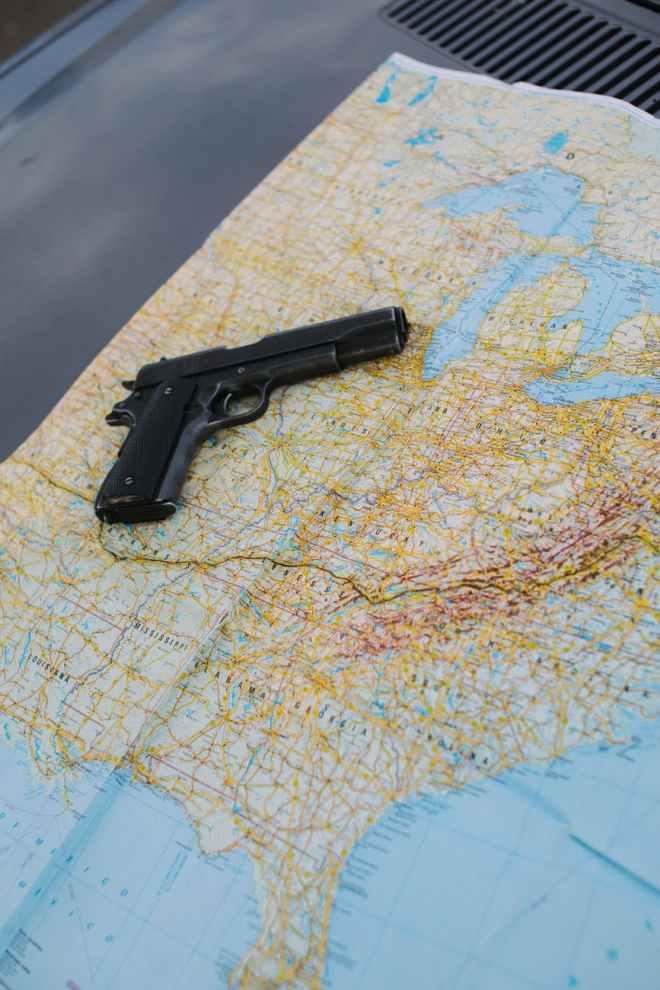 black semi automatic pistol on white and blue textile