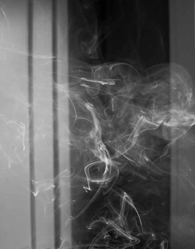 cigarette smoke floating in dark room