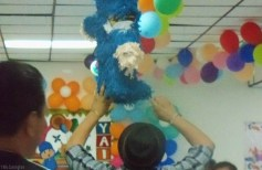 After a few more whacks the arm is so damaged that the piñata is considered vanquished, and the adults help release the candy.