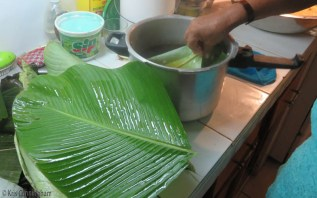 Dipping bijao leaves in the hot water to soften them.