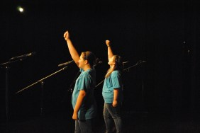 Eighth graders Rebecca Reeves and Megan Poe finish their solos with their fists in the air.