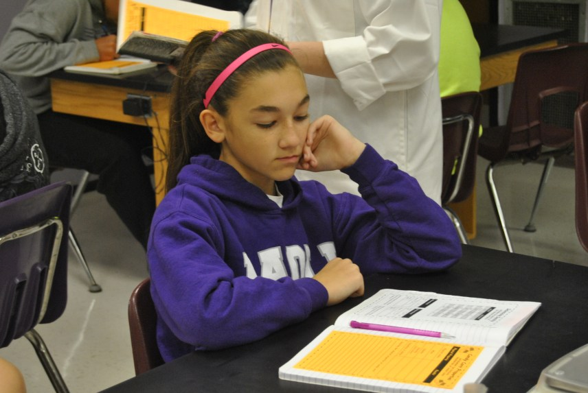Eighth grader Kaylee Schneider listens to her science teacher to know what to do.