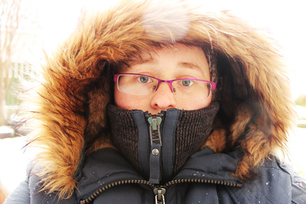 Photograph of girl from 2015 looking into camera wearing heavy jacket with fur hood.