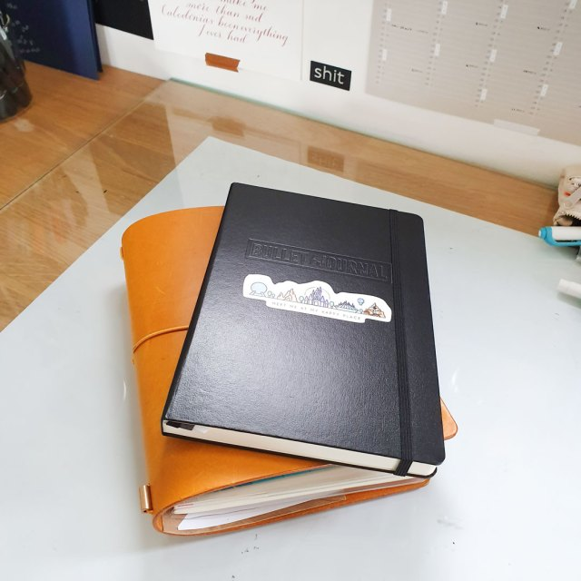 Image shows a bullet journal and traveller's journal resting on a worktop.