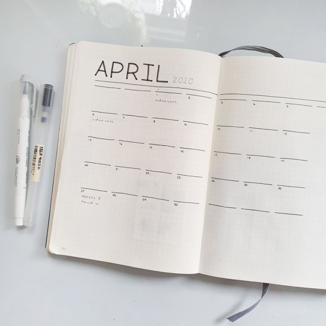 Image shows notebook resting on worktop displaying monthly calendar spreads.